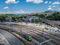 Blick auf einen grünen Zug der gerade in das Schienennetz in Bern einfährt